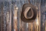 felt cowboy hat hanging on barn wall - 147170718