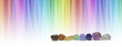 Healing chakra crystals and color healing website header -  A  row of eight chakra colored tumbled crystals and against a linear graduated chakra rainbow color background with  copy space