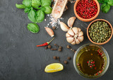 Selection of spices and herbs - garlic, salt, pink, green and black pepper, lemon, Basil, olive oil. Ingredients for cooking. Food background on black table slate. Top view copy space. - 147381920