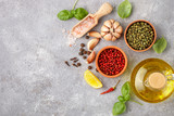 Selection of spices and herbs - garlic, salt, pink, green and black pepper, lemon, Basil, olive oil. Ingredients for cooking. Food background on grey  table slate. Top view copy space - 147381981