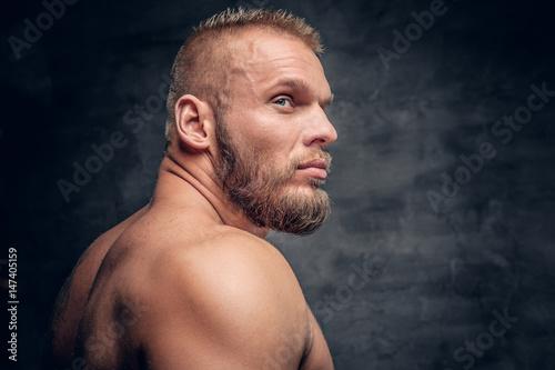 Studio portrait of brutal bearded muscular male over grey vignette background.