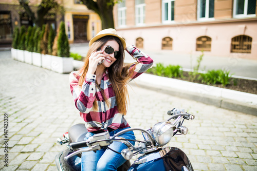 Pretty young woman in hat using smartphone while sitting on motorbike Poster