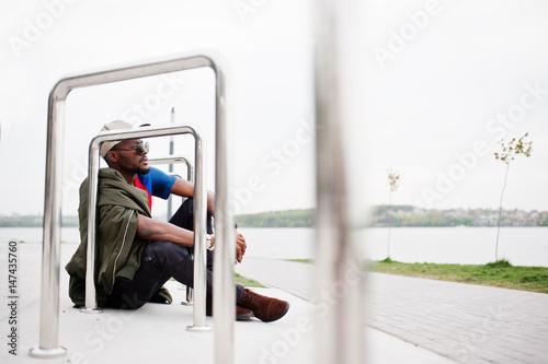 Juliste Stylish african american boy wear at cap, football t-shirt and sunglasses sitting near steel railings