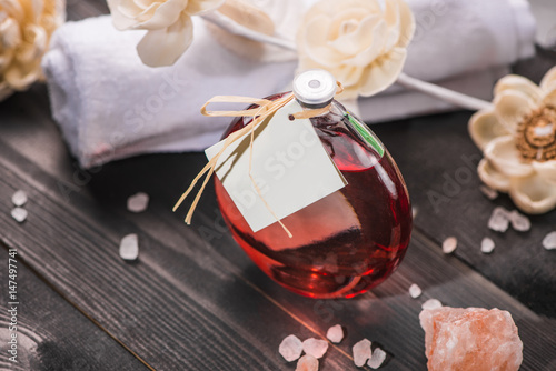 Spa decoration. Bottle of essential oil and draft flowers.