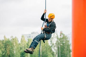 Industrial climber in uniform and helmet rises. Risky job.