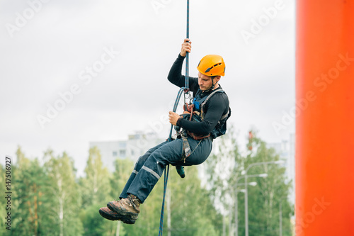 Industrial climber in uniform and helmet rises. Risky job.