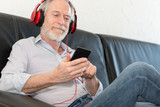 Modern mature man listening music on mobile phone