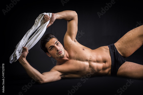 Juliste A handsome latin young man lying naked on the floor, wearing only underwear