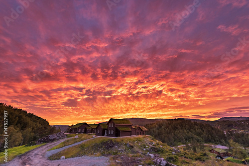 Deurstickers Koraal Burning Sky in Norway. Local Village Architecture and Red Sky.