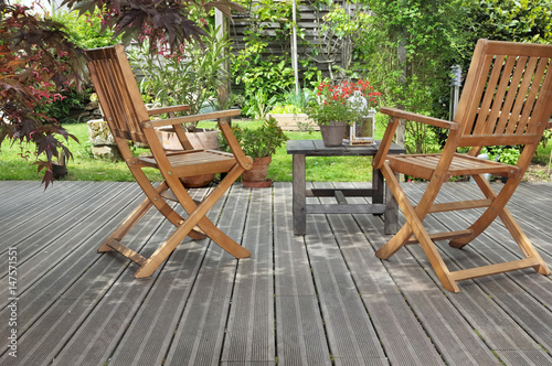 chaises et table sur terrasse en bois donnant sur jardin