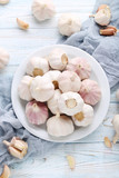 Garlic in plate on blue wooden table - 147575310