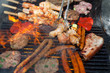 Delicious assortment of meat and vegetables grilling on a BBQ with pork sausages, chops, skewers with mixed kebabs - 147654174