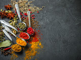 Variety of natural spices, seasonings and herbs in spoons on the stone table.  Top view with copy space - 147658309