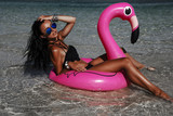 Fototapety A beautiful sexy amazing young woman on the beach sits on an inflatable pink flamingo and laughs, has a great time, tanned perfect body, long hair, black bikini, fashion accessories, low key photo