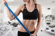 Sporty young woman usind elastic band during stretching workout at gym