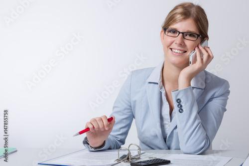 Junge frau sitzt am schreibtisch und telefoniert lachend for Schreibtisch 90x60