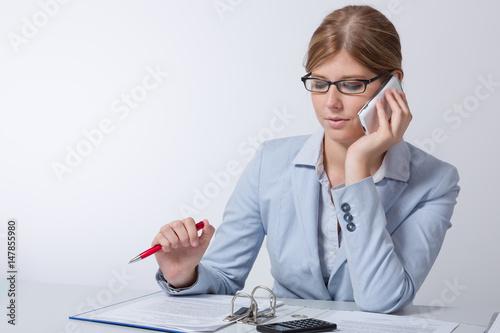 Junge frau telefoniert am schreibtisch mit unterlagen for Schreibtisch 90x60