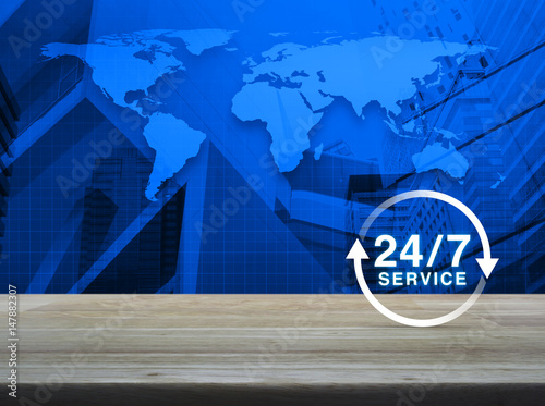 Poster 24 hours service icon on wooden table over world map and city tower background,