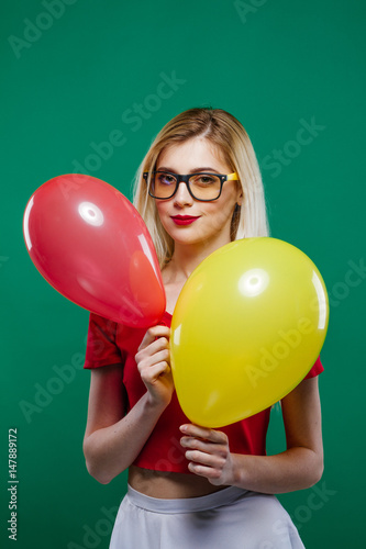 Poster Funny Joyous Girl Hides Behind the Red and Yellow Balloons, then Suddenly Appears and Smiles Widely Looking in the Camera