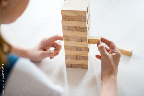 Close-up partial view of girl playing jenga game on white table плакат