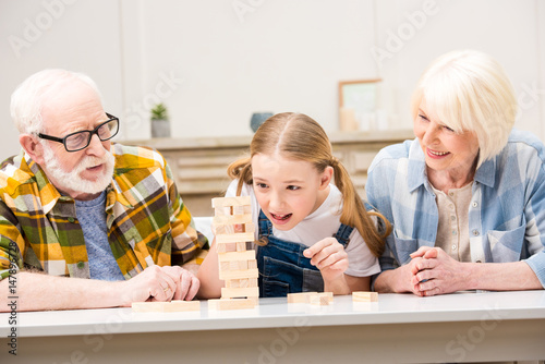 Happy grandparents with granddaughter playing jenga game together at home плакат