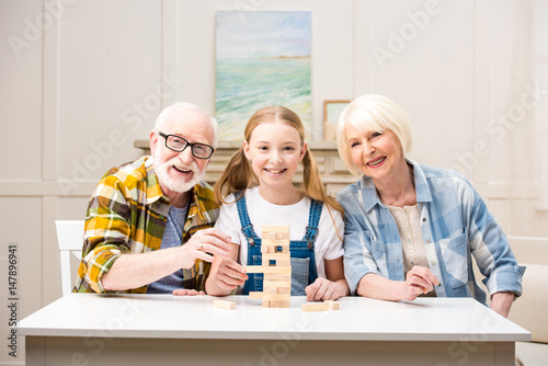 Happy family playing jenga game together and smiling at camera плакат