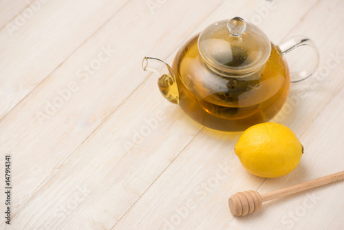 Cup of lemon tea with honey on white wooden background. Poster