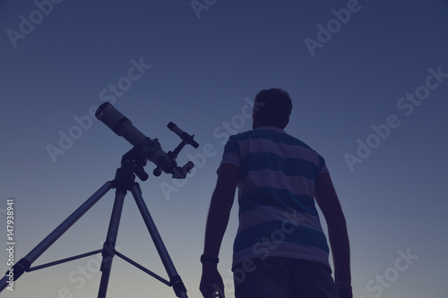 Man looking at the night sky through a telescope. - 147938941