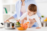 Fototapeta happy mother and baby cooking vegetables at home