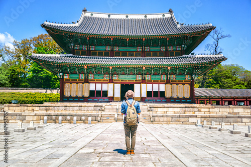 girl tourist with a backpack standing in front of a beautiful historic pagoda Poster