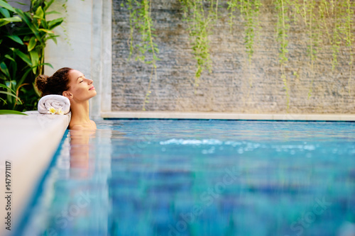 Leinwanddruck Bild Beauty and body care. Sensual young woman relaxing in outdoor spa swimming pool.