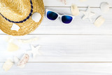 Summer Beach accessories (White sunglasses,starfish,straw hat,shell) on white plaster wood table top view,Summer vacation concept,Leave space for adding text - 148011529