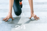 partial view of sportswoman in starting position on stadium stairs, fitness woman running concept