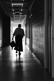 Silhouette of a man in the long corridor of the sports center after training aikido