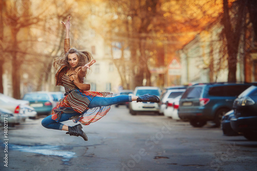 Dancer woman jumping on the streets of city