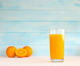 Orange juice in a glass on a wooden background. Fresh fruit from summer