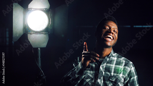 Young African-American man in darkness coming close to camera, then studio light stand is being turned on making man happy and smiling. Looking at camera