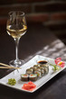 Sushi rolls on white plate and glass of wine