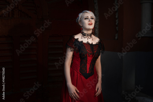 Woman with a vampire fangs, she is dressed in a red dress with lace Poster