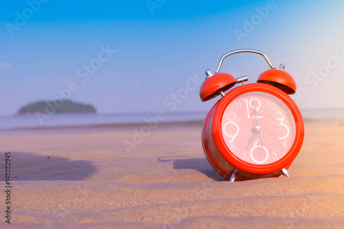 closeup of an alarm clock on the sand of a beach adjusting morning  of the summe Poster