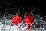 Two red apples in water splash on black background