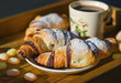 Breakfast still life, fresh croissants and cup of morning coffee on a wooden tray