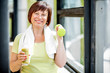 Happy older woman in sports wear training with dumbbells indoors on the window background