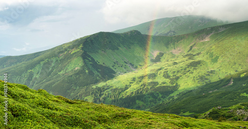 Rainbow under mountain ridge. Panoramic landscape in the summer time
