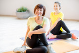 Young and older women in sports wear doing yoga together indoors at home or a gym