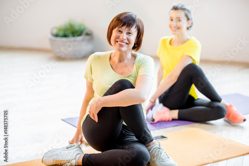 Obraz na płótnie Young and older women in sports wear doing yoga together indoors at home or a gym