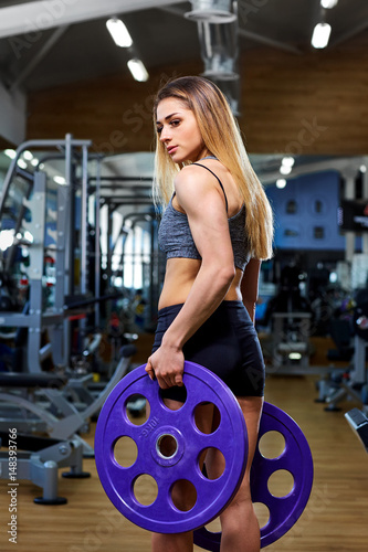 Póster Girl athlete with a barbell in the hands of the gym.