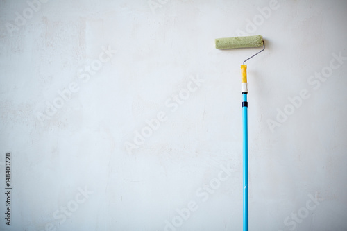 Background of paint roller standing against blank white wall