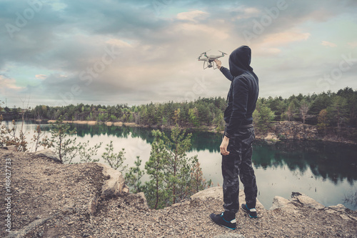 Juliste The man in dark pants and a jacket holding quadrocopter in his hands before takeoff on the background of a forest lake