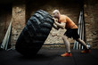 Full-length portrait of middle-aged athlete focused on intensive training while flipping huge tire, profile view